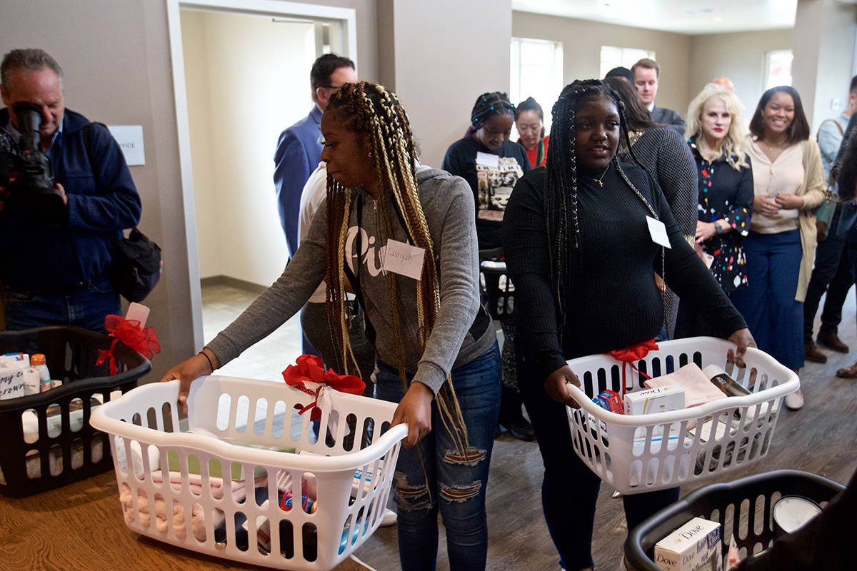 Cassiyah Holmes, left, and Kiara Malone, both seniors at Life Learning Academy, pick up gift laundry baskets provided by Mayor London Breed during a tour of the new student dormitory at the school on Treasure Island on Wednesday, Aug. 7, 2019.