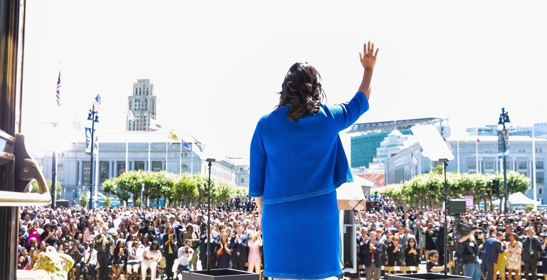 Photo from behind Mayor London Breed as she waves to the crowd at her inauguration