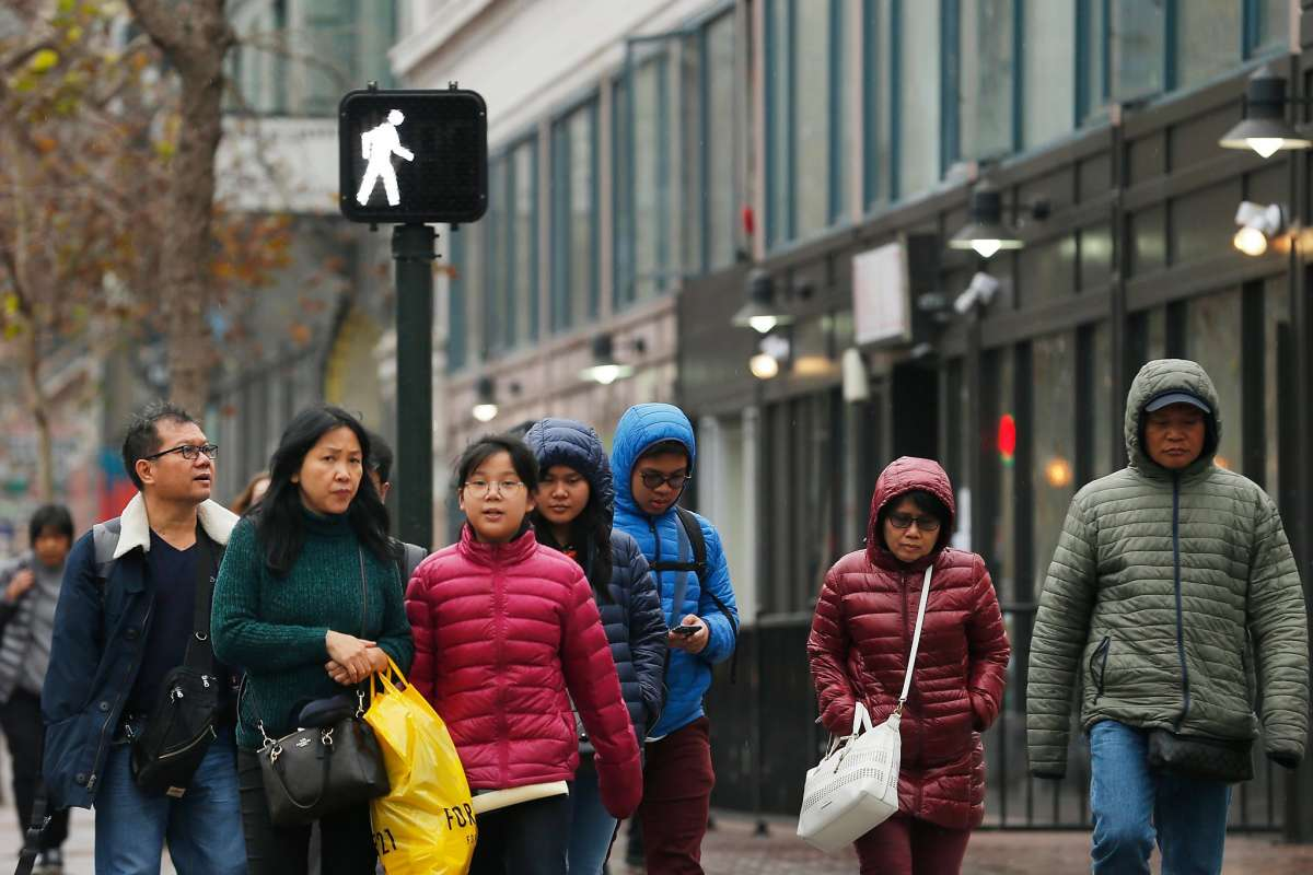 Pedestrians cross the street at Market and 6th streets