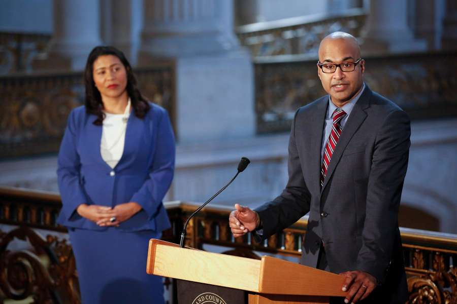 Manohar Raju, selected by Mayor London Breed (left) as the city's new public defender, speaks to the media at City Hall.
